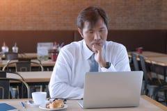 Poważny Azjatycki biznesmen używa laptop przy kawą podczas gdy siedzący Zdjęcie Royalty Free