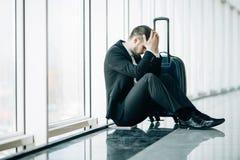 Poważny biznesmen martwi się coś, siedzący i dotyka jego głowę przy lotniskowym terminal Biznesmena chybienie jego lot Młody czło fotografia stock