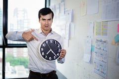 Poważny biznesmen trzyma dużego zegar w jego rękach, czas pracować Zdjęcia Royalty Free
