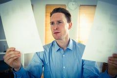 Poważny biznesmen trzyma dwa papierowego prześcieradła Fotografia Stock