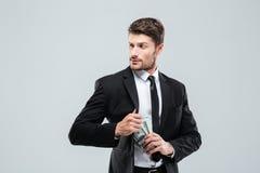 Poważny biznesmen w kostiumu i krawacie chuje pieniądze w kieszeni Obraz Stock