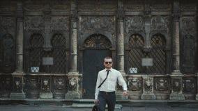 Poważny biznesmen załatwia jego z teczką przed budynkiem biurowym krawat zbiory