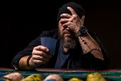 Poważny brodaty mężczyzna obsiadanie przy grzebaka mieniem i stołem grępluje odosobnionego na czerni Obrazy Royalty Free