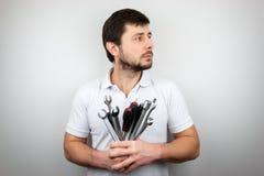 Poważny brodaty mężczyzna patrzeje strona w białej koszulce z bukietem wyrwania i śrubokręty fotografia royalty free