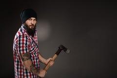 Poważny brodaty woodcutter trzyma cioskę obraz stock