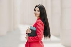 Poważny brunetka bizneswoman z makeup, manicure, jest ubranym czerwoną kurtkę, niesie dzienniczek i notepad, stojaki w profilowy  obraz stock