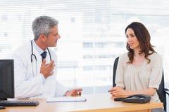 Poważny cierpliwy opowiadać z jej lekarką o chorobie zdjęcie stock