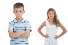 Poważny dziecko pozuje podczas gdy jego siostry ono uśmiecha się Obraz Stock