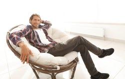 Poważny facet odpoczywa obsiadanie w wielkim wygodnym krześle Boczny widok zdjęcia royalty free