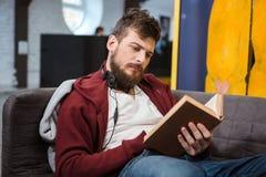 Poważny faceta obsiadanie na kanapie i czytaniu książka Obrazy Royalty Free