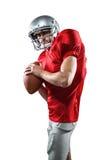 Poważny futbolu amerykańskiego gracz w czerwonej dżersejowej mienie piłce Zdjęcia Stock