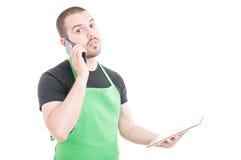 Poważny hypermarket urzędnik opowiada przy telefonem i trzyma pastylkę Obraz Royalty Free