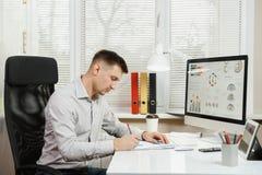 Poważny i engrossed biznesowy mężczyzna w koszulowym obsiadaniu przy biurkiem, pracuje przy komputerem z nowożytnym monitorem Kie Obraz Royalty Free
