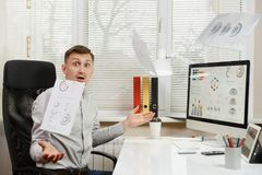 Poważny i engrossed biznesowy mężczyzna w koszulowym obsiadaniu przy biurkiem, pracuje przy komputerem z nowożytnym monitorem Kie Obrazy Stock