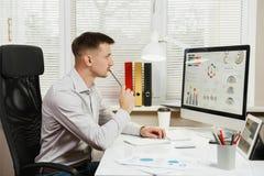 Poważny i engrossed biznesowy mężczyzna w koszulowym obsiadaniu przy biurkiem, pracuje przy komputerem z nowożytnym monitorem Kie Zdjęcia Royalty Free