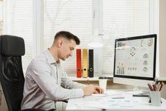 Poważny i engrossed biznesowy mężczyzna w koszulowym obsiadaniu przy biurkiem, pracuje przy komputerem z nowożytnym monitorem Kie Fotografia Stock