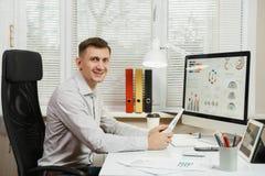 Poważny i engrossed biznesowy mężczyzna w koszulowym obsiadaniu przy biurkiem, pracuje przy komputerem z nowożytnym monitorem Kie Zdjęcie Royalty Free