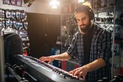 Poważny i skoncentrowany młody człowiek bawić się na klawiaturze Słucha muzyka przez hełmofonów Ja jest pogodny wśrodku fotografia stock