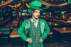 Poważny i skoncentrowany młody człowiek w zielonym kostiumu samodzielnym w pubie Trzyma ręki na biodrach i patrzeje na kamerze Fa zdjęcia stock