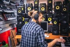 Poważny i skoncentrowany oyung mężczyzna tworzy muzykę w studiu Nagrywa muzykę bawić się na klawiaturze Modniś praca przy obrazy stock
