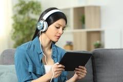 Poważny kobiety dopatrywanie i słuchający wideo na pastylce fotografia stock