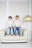 Poważny mąż i żona siedzimy na plecy białej skóry kanapa Fotografia Stock