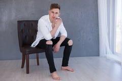 Poważny mężczyzna fashionl lookon krzesła photoshoot obraz royalty free