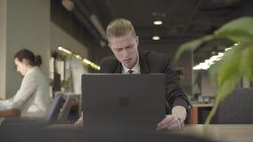 Poważny mężczyzna kaukaski pracownik biurowy siedzący przy stole i otwierający laptop Portret rudogłowy w oficjalnym garniturze zbiory wideo