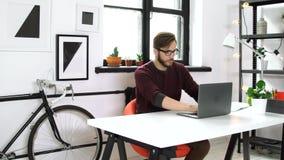 Poważny mężczyzna pisać na maszynie na laptopu obsiadaniu w biurze zbiory wideo