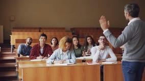 Poważny mężczyzna szkoły średniej nauczyciel opowiada ucznie wtedy młody facet w szkłach podnosi rękę i pyta pytanie zbiory wideo