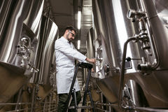 Poważny mężczyzna używa drabinę i browarnianego mechanizm przy fabryką Fotografia Royalty Free
