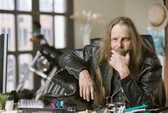 Poważny mężczyzna w jego biurze z motocyklem i hełmem obraz royalty free