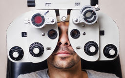Poważny mężczyzna w phoropter z oko cechunkiem Zdjęcia Royalty Free