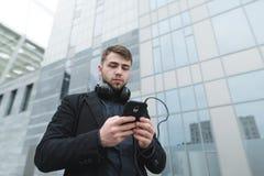 Poważny mężczyzna wybiera muzykę na jego telefonie przeciw tłu miastowy krajobraz z hełmofonami na jego szyi zdjęcie royalty free