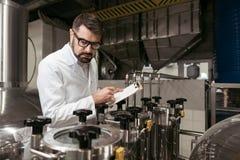 Poważny mężczyzna zauważa pracę wynika na piwnej fabryce obrazy royalty free