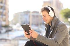 Poważny mężczyzny dopatrywanie i słuchający środki na pastylce zdjęcia royalty free