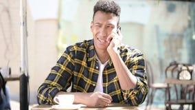Poważny młody afrykański mężczyzna opowiada na telefonie, plenerowa kawiarnia zbiory