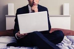 Poważny młody biznesmen pracuje na laptopie w pokoju hotelowym obraz stock