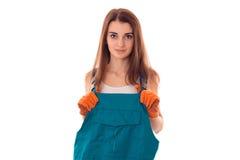 Poważny młody brunetki kobiety budowniczy w mundurze z rękawiczkami robi odświeżaniu i patrzeć kamerę odizolowywającą na bielu Zdjęcie Royalty Free