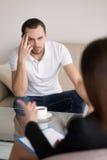 Poważny młody człowiek słucha żeński psycholog, advisor lub c, Zdjęcia Stock