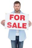 Poważny młody człowiek trzyma a dla sprzedaż znaka Obraz Stock