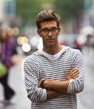 Poważny przyglądający młody człowiek na ulicie Zdjęcia Royalty Free