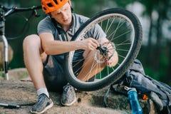 poważny młody próbny rowerzysta załatwia rowerowego koło outdoors podczas gdy siedzący obrazy stock