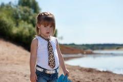 Poważny mały model pozuje na jeziornym tle Fotografia Stock