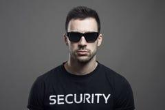 Poważny markotny portret jest ubranym okulary przeciwsłonecznych patrzeje kamerę pracownik ochrony Fotografia Stock