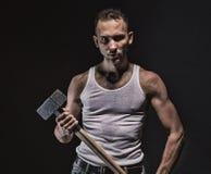 Poważny mięśniowy mężczyzna z młotem Fotografia Stock