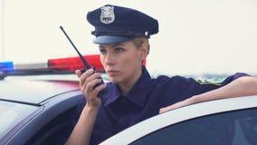Poważny milicyjny kobiety dostawanie wzywa radio set, dostaje w samochód i śpieszyć się zbiory