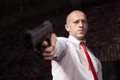 Poważny najęty morderca w czerwonym krawacie celuje pistolet Obrazy Royalty Free