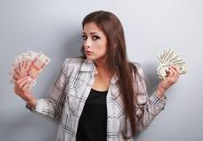Poważny nieszczęśliwy biznesowej kobiety główkowanie który waluta wybierać, Fotografia Royalty Free