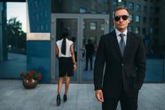 Poważny ochroniarz w kostiumu i okularach przeciwsłonecznych chroni, fotografia stock